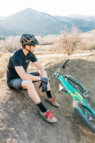 Mountain bike rider sitting on a berm with his bike and mountains in the background.