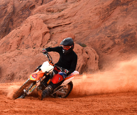A guy riding a ktm dirt bike in the red sand in southern Utah.