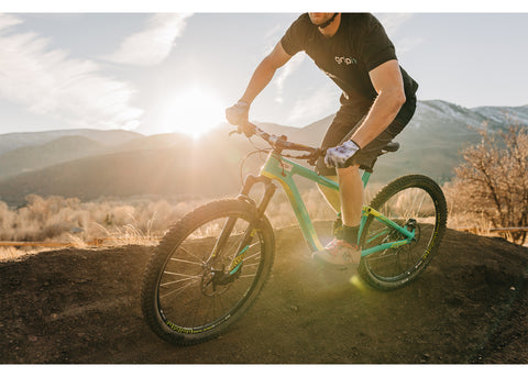 A guy wearing Gripit Gloves riding a mountain bike with a mountain sunset in the background.
