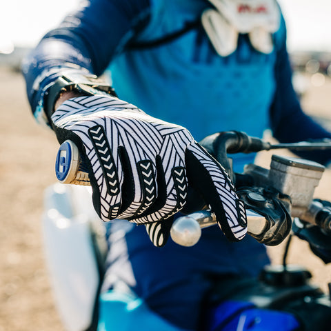 A motocross rider grabbing the bars of his dirt bike while wearing a black and white striped Gripit glove.