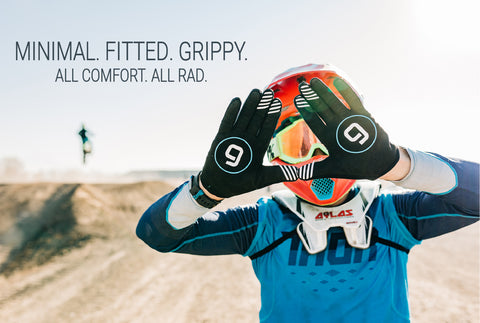 A motocross rider with his hands up, palms out, showing his Gripit glove.