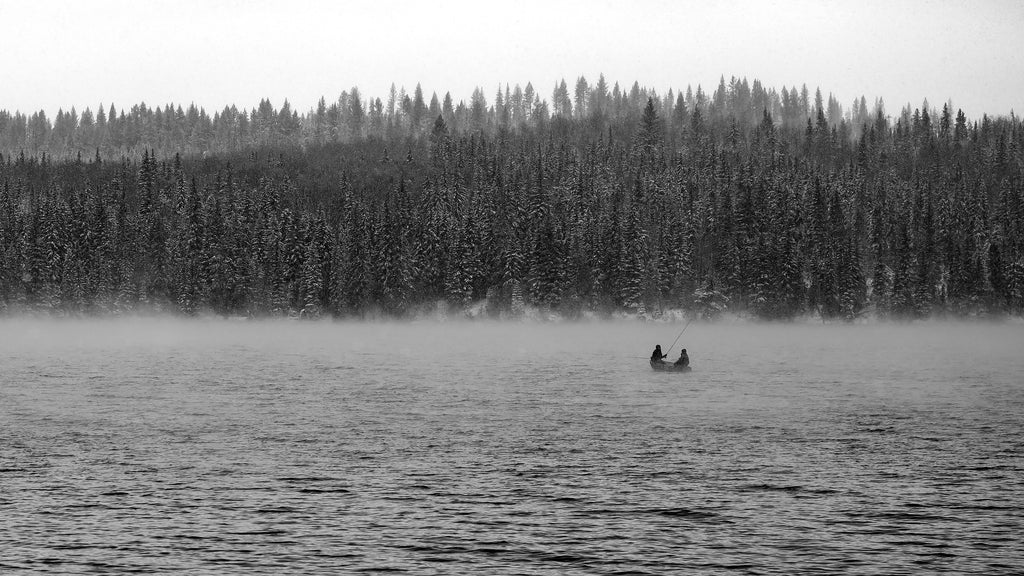 Black and white landscape image of misty cold lake with fisherman in a boat.