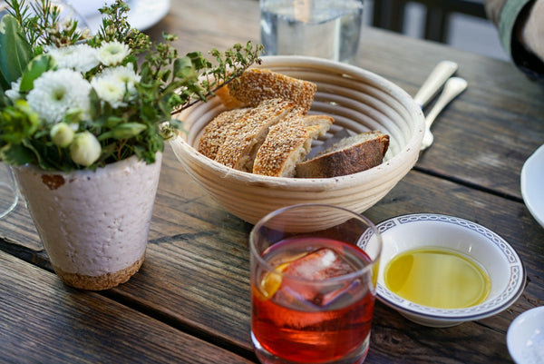 Table with flowers, bread, olive oil and drink
