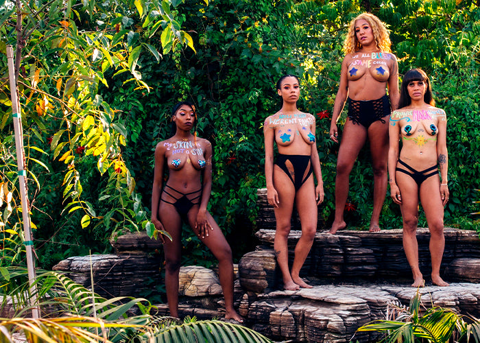 Four black women standing on rocks in front of green foliage wearing pasties with black lives matters phrases written across their chest