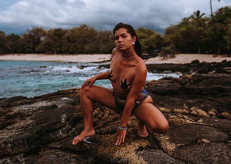 Woman wearing weed pasties and swim bottoms crouch on rocks by the ocean