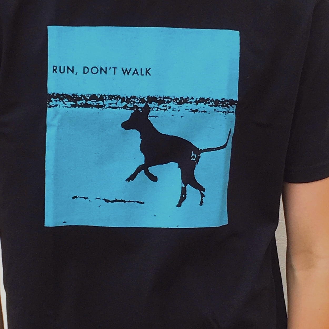 Photograph of screenprinted t-shirt depicting a prancing dog at Leighton Beach, Western Australia.