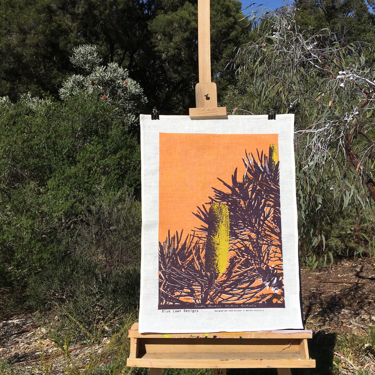Photograph of a candle banksia tea towel on an easel in the bush.