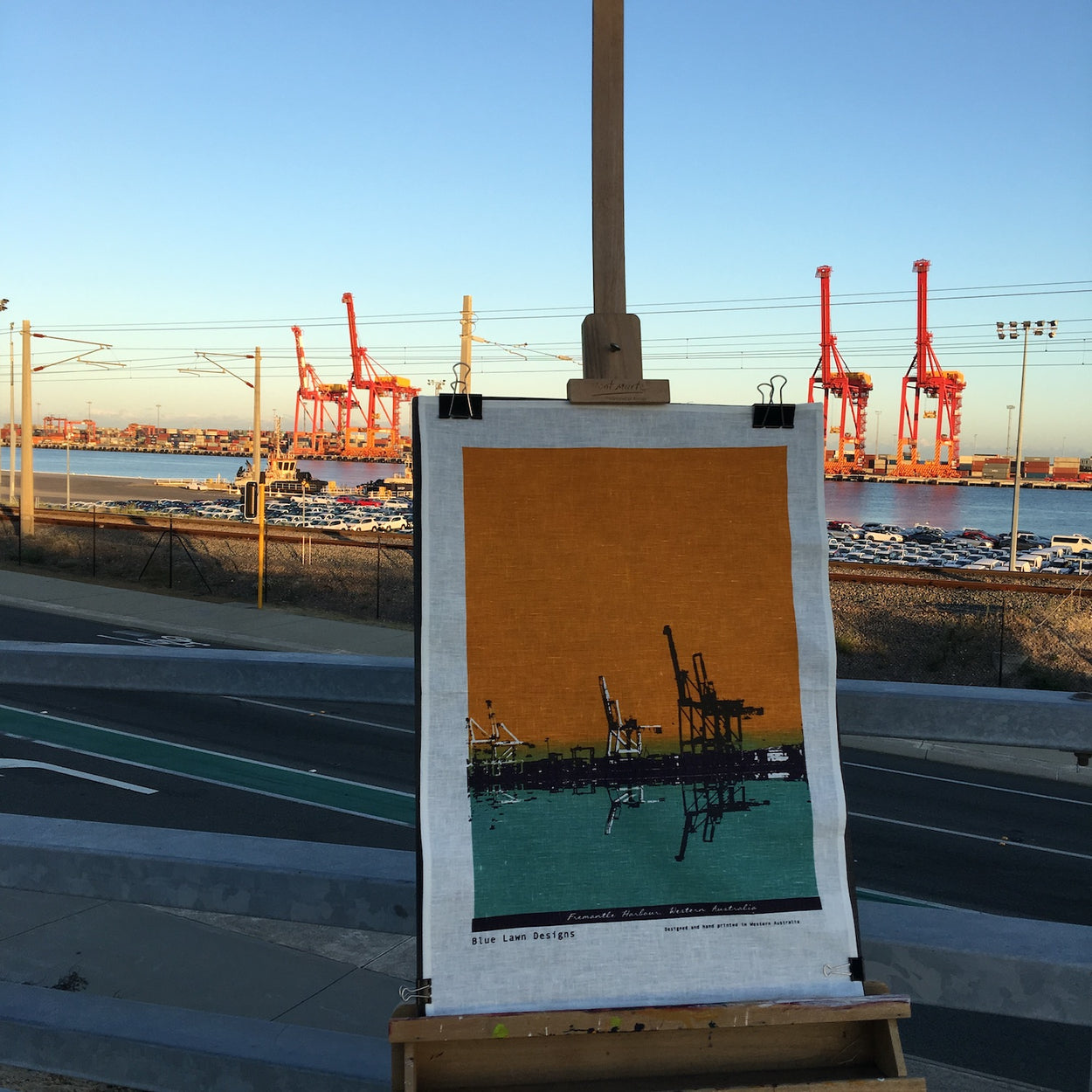 Photo of a Fremantle Harbour tea towel on an easel.