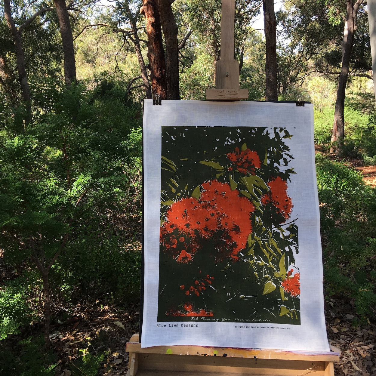 Photograph of a red flowering gum tea towel on an easel in a forest setting.