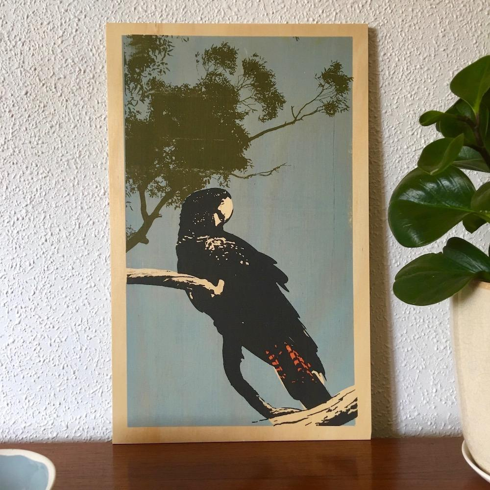 Photo of a red-tailed black cockatoo screenprinted on plywood.