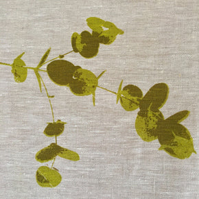 Photograph of eucalyptus leaves screenprinted on linen in close-up.