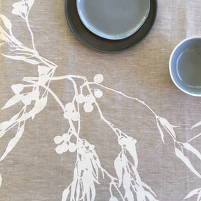 Photo of screenprinted tablecloth depicting eucalyptus flowers and leaves in close-up.