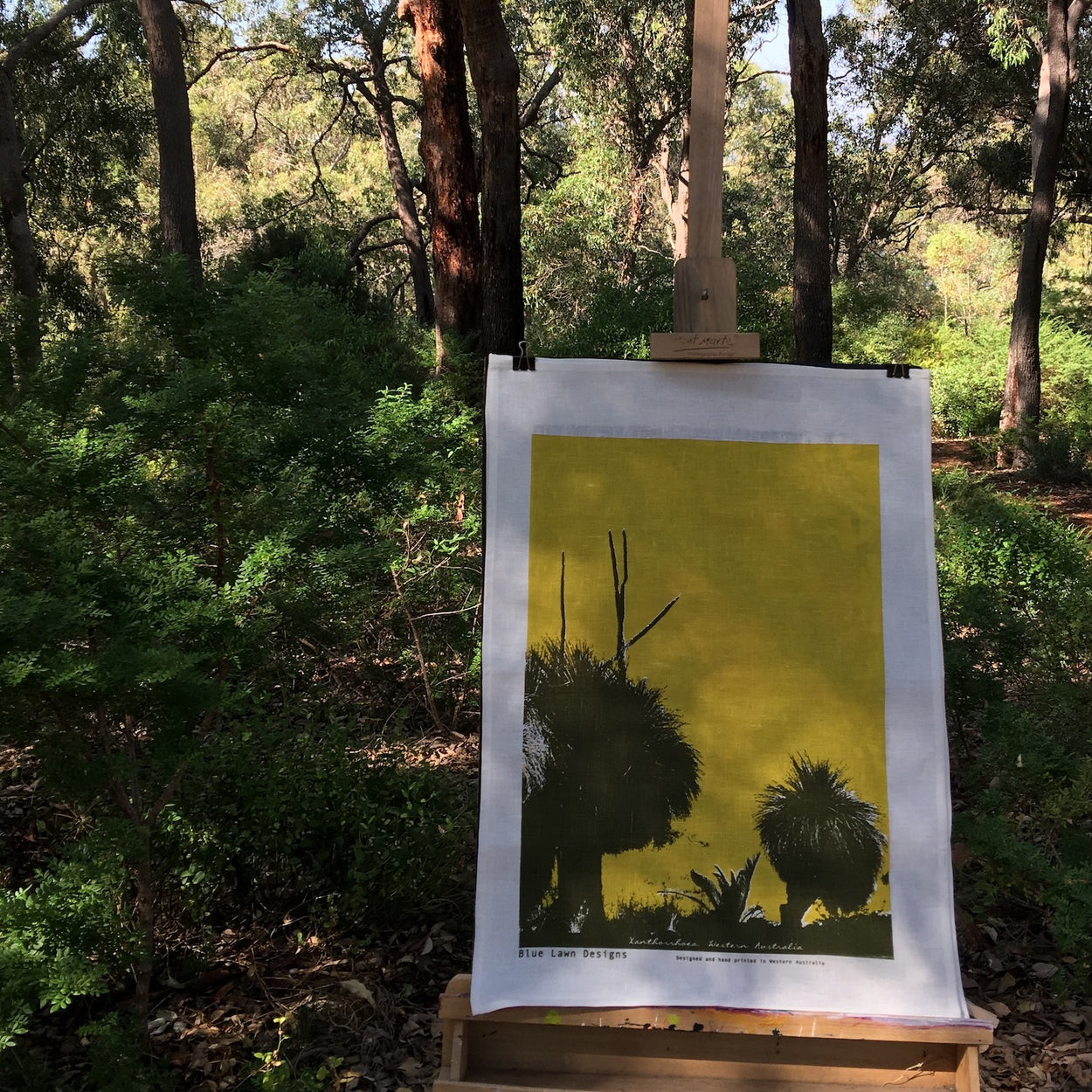 Photograph of a grass trees tea towel on an easel in the forest.