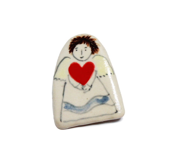 a small pale ceramic brooch with a simple painted angel holding a red heart