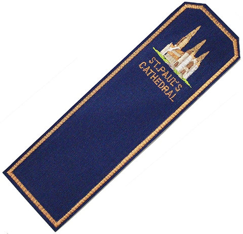 a dark blue fabric bookmark with an embroidered gold border and simplified image of the cathedral and the words St Paul's cathedral.