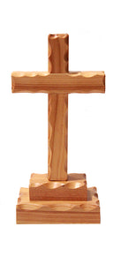 a small wooden cross with scalloped edges fixed to a base of two wooden blocks