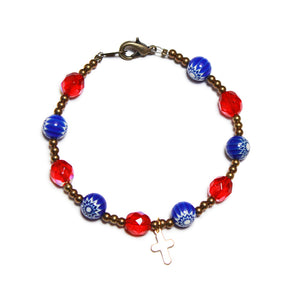 a 10 bead bracelet of alternating red faceted crystal beads and dark blue glass beads incorporating a small gold plated cross