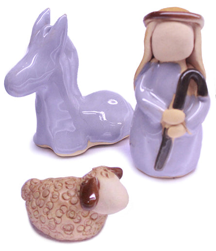 Shepherd figure has pale grey glaze and holds a crook. sitting donkey figure has pale grey glaze. seated sheep is a light brown textured finish.