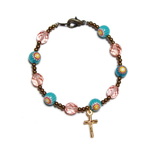 a 10 bead rosary bracelet of faceted pink crystal and pale blue flower beads incorporating a tiny gold plated crucifix