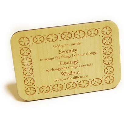 A small rectangular standing plaque made of wood etched with the serenity prayer and a four leafed clover design around the edge