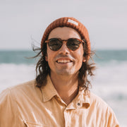 Mari & Clay sunglasses with male model wearing the Goulburn style in caramel colour frames and dark-green polarised lenses. The Goulburn is a classic round design, with thin rims to make it extra lightweight. Our sunglasses are crafted with high-quality bio-acetate and polarised lenses. Designed in Australia.