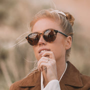 Female model wearing Mari & Clay Sustainable Sunglasses in Goulburn Style in tortoiseshell. Mari & Clay sunglasses are crafted from bio-acetate and fitted with brown polarized lenses. The Goulburn is a classic round design with thin rims to make it extra light-weight. Designed in Australia.