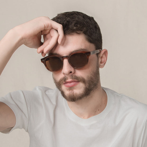 Male model wearing Mari & Clay Sustainable Sunglasses Murray Style in caramel colour frames with brown polarized lenses. The design is square shape with rounded corners. Designed in Australia. Crafted from sustainable bio-acetate material.