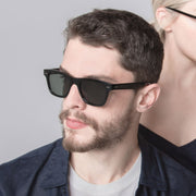 Male model wearing Mari & Clay Sustainable Sunglasses Yarra Style in black colour frames with dark-green polarized lenses. These sunglasses are trapezoidal shape with thicker arms. Designed in Australia. Made with bio-acetate.
