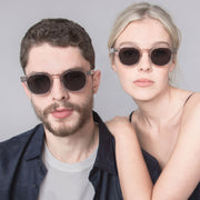 Female and male model wearing Mari & Clay Sustainable Sunglasses Murray Style in transparent sand colour frames with grey polarized lenses. The design is square shape with rounded corners. Designed in Australia. Crafted from sustainable bio-acetate material.