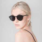 Mari & Clay sunglasses with female model wearing the Goulburn style in black colour frames and dark grey polarised lenses. The Goulburn is a classic round design, with thin rims to make it extra lightweight. Our sunglasses are crafted with high-quality bio-acetate and polarised lenses. Designed in Australia.