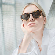 Female model wearing Mari & Clay Sustainable Sunglasses Murray Style in tortoiseshell colour frames with dark-green polarized lenses. The design is square shape with rounded corners. Designed in Australia. Crafted from sustainable bio-acetate material.