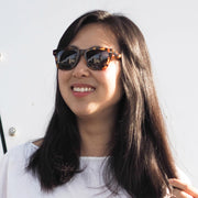 Female model wearing Mari & Clay Sustainable Sunglasses Yarra Style in tortoriseshell colour frames with grey polarized lenses. These sunglasses are trapezoidal shape with thicker arms. Designed in Australia. Made with bio-acetate.