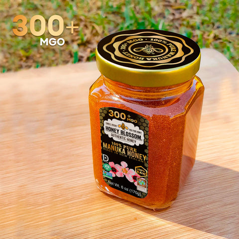 """Image of Manuka jar on a wooden table and grass in the background with text referring to """"300+ MGO""""."""