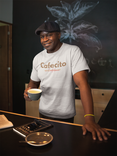 "Smiling Black man in coffee shop standing up with mug in hand. He has a hat on and a white shirt that says ""Cafecito and Confidence"""