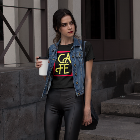 "Fashionable Woman with red lipstick, a denim vest, and leather leggings walking downstairs in heels with a to-go latte in hand. Wearing our comfortable and stylish ""Cafe"" Tee"