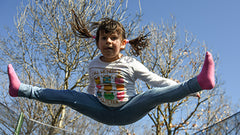 A picture of a young girl jumping and doing the splits in the air.