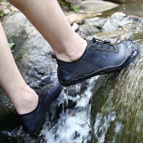 water shoes worn by model with feet on a small waterfall