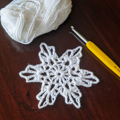 Crochet snowflake with yarn and hook
