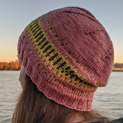 A pink colourwork hat, on a head with person looking out to the river