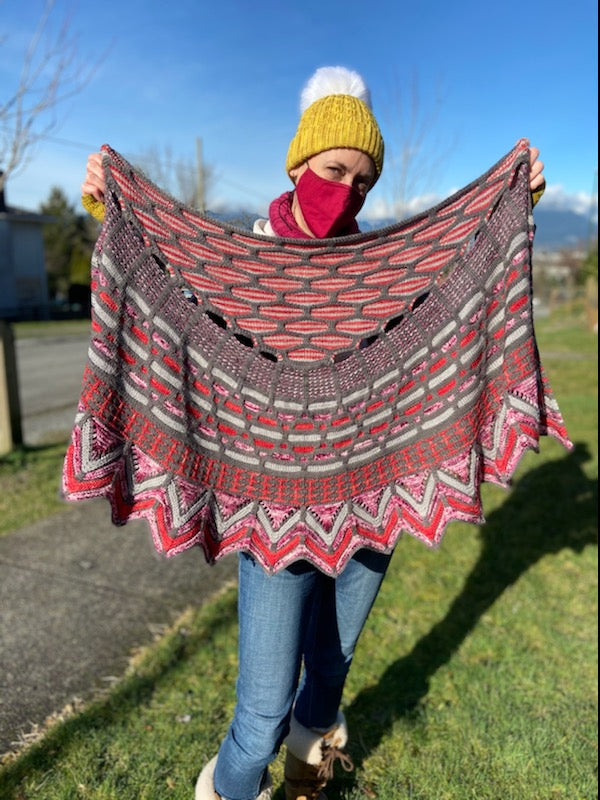 Stephen West's Slipstravaganza shawl being held up by a person wearing a yellow hat