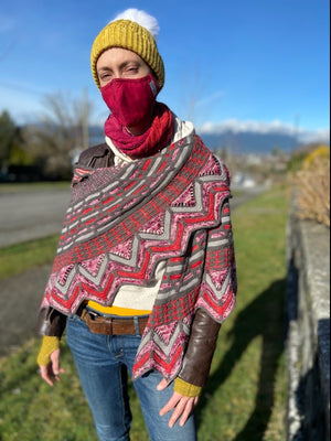 Stephen West's Slipstravaganza shawl wrapped around a persons shoulders wearing a yellow hat