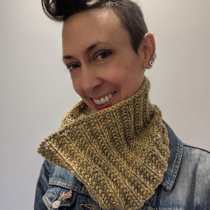 Person smiling wearing a hand knitted bulky weight cowl