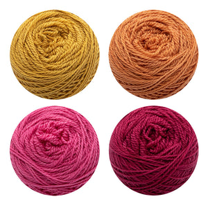 4 cakes of naturally dyed yarn in yellow, orange, pink and red.