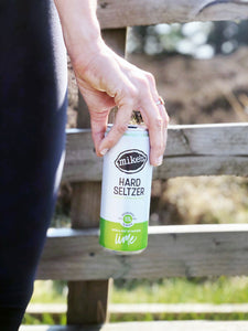 Hand holding Mike's Hard Lime Seltzer with fence in background
