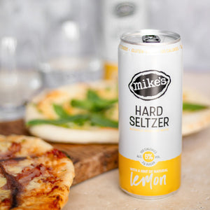 Mike's Hard Lemon Seltzer Can with Pizza in background