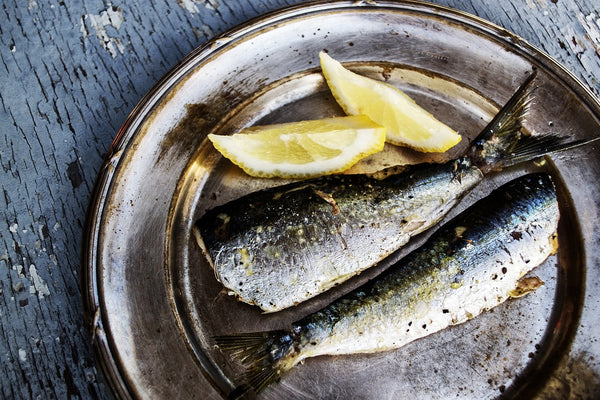 Best keto diet snacks: sardines on a plate with lemon wedges