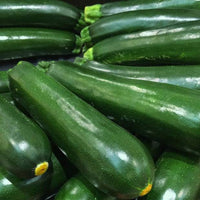A large pile of glossy dark green zucchini squash fruit