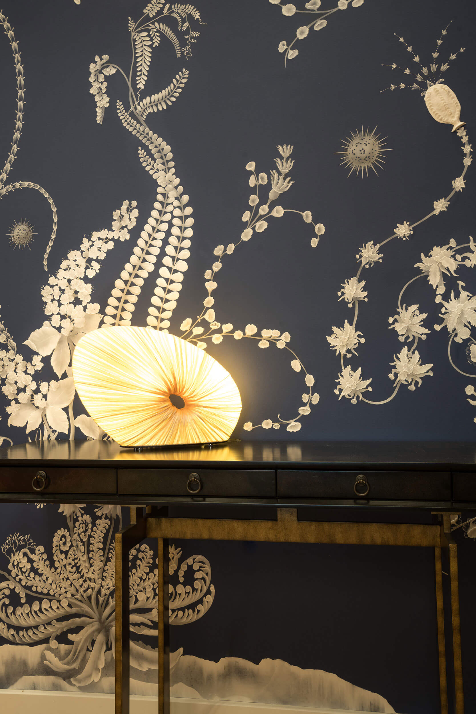 Doe Table Lamp in Cream silk on a dark wooden table against a dark blue wallpaper decorated with golden flower motifs