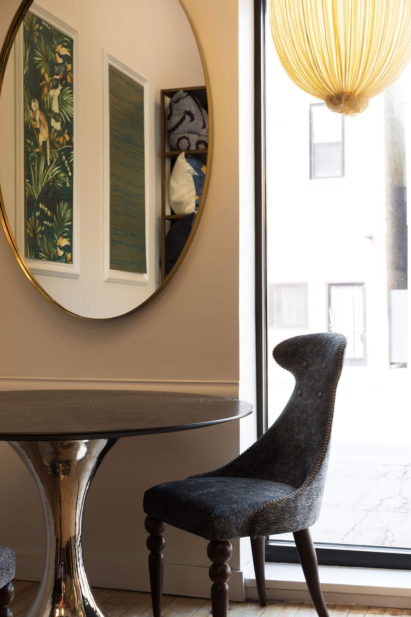 Dippa Pendant Light hanging above a dark, cushioned chair, next to a round wooden table and a circular mirror