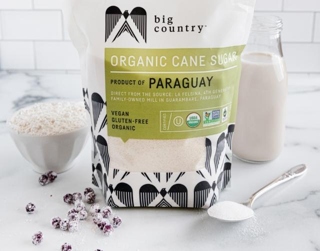 Bagged Big Country organic cane sugar sitting on a white marble counter beside other organic ingredients